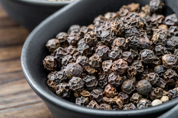 Black pepper, peppercorns in black bowl close up