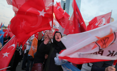 AK Party supporters wave flags in front of the AKP headquarters in Ankara