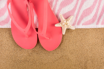 Pink sandal flip flop and towel on sand beach and starfish. Summer vacations copy space and concept. Top view, close up