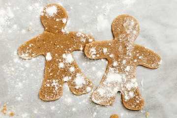 Preparation of ginger biscuits. Cutting figured cookies in the form of gingerbread man.  New Year's Eve symbol.