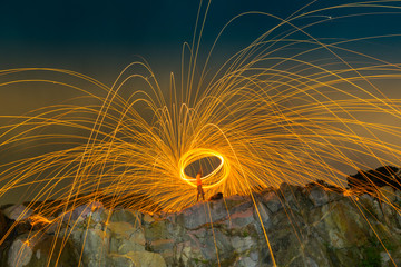 burning steel wool on the mountain rock above lagoon