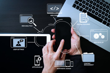 cyber security internet and networking concept.Businessman hand working with mobile phone on laptop computer background