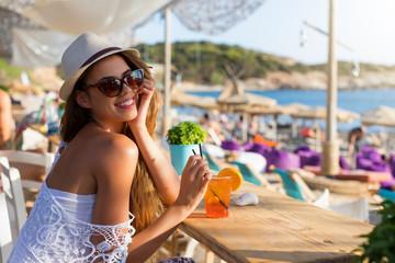 Junge, blonde Frau sitzt in einer Strandbar bei Athen, Griechenland, und genießt ihren Urlaub