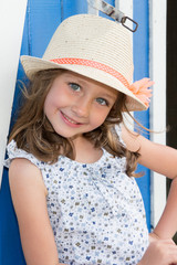Smiling cute child girl 4-5 year old wearing flowers dress clothes posing in garden outdoors with straw hat