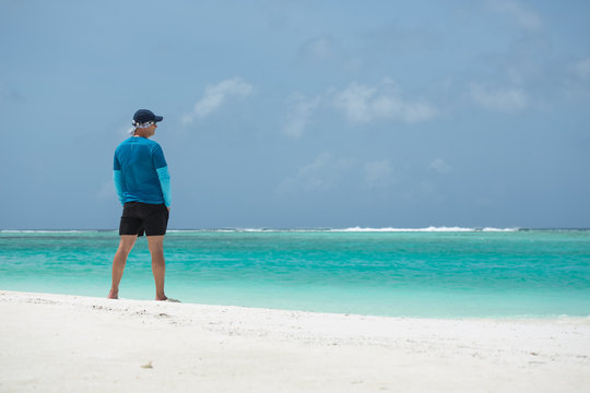 A man stands on the beach and looks out to sea