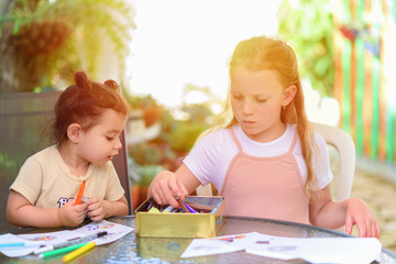 Two cute little sisters drawing with colorful pencils at backyard summer sunny garden. Creative kids painting together. Girls doing homework at home, choosing a pencil.