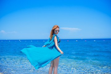 Beautiful Girl at warm country. Travel and Vacation. Freedom Concept. Sensual red hair beautiful woman, lady with perfect fashionable body figure ,Marine style