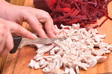 Sliced boiled turkey meat. Female hands with a knife cut boiled turkey meat