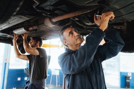 Mechanics fixing car exhaust system in garage