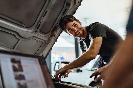 Car mechanics working at auto repair shop