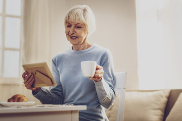 Pleasant memories. Joyful elderly woman looking at the photo while having a cup of coffee