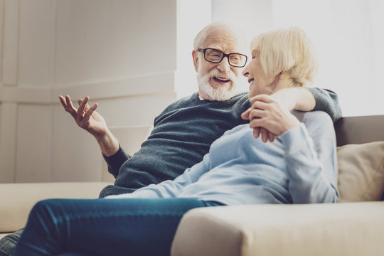 Aged couple. Joyful aged woman looking at her beloved man while listening to his jokes