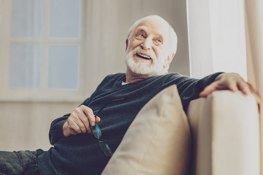 Pleasurable time. Joyful senior man smiling while enjoying his rest at home