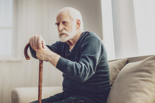 Time to think. Sad aged man sitting on the sofa and thinking about his life