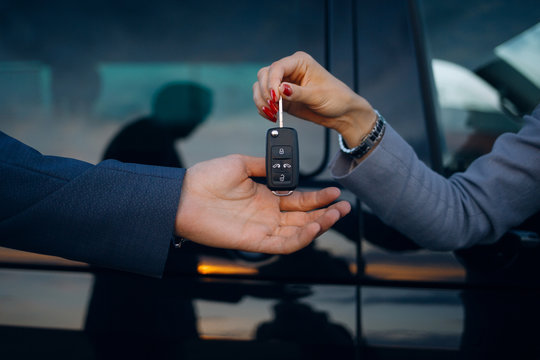 Woman give cars key to man. Hands hold car keys. Car rental