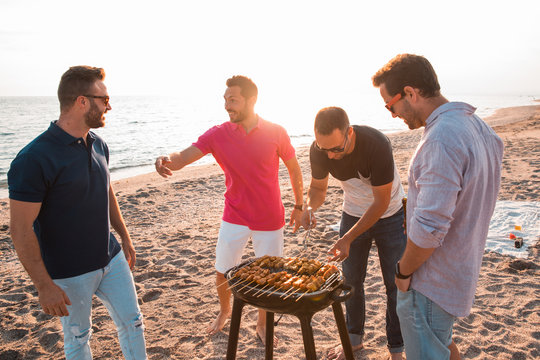 Happy friends are having fun while they are preparing a barbecue on the beach. Vacation concept.
