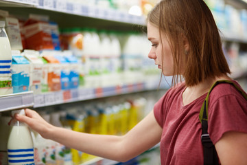 Cropped shot of beautiful young female shops for dairy products in grocery store, rakes bottle of milk, eats healthy food, stands sideways at camera, has serious expression. People and buying