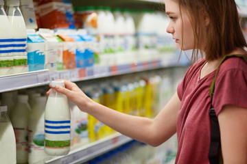 Horizontal view of serious beautiful young female chooses milk products in dairy deparment of supermarket, dressed in casual t shirt, has short hair. People, lifestyle and consumerism concept