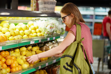 Sideways shot of beautiful young woman with bag, chooses fruits in grocer`s shop, touches to lemons, make purchases in supermarket, eats healthy food. People, consumerism and buying concept.