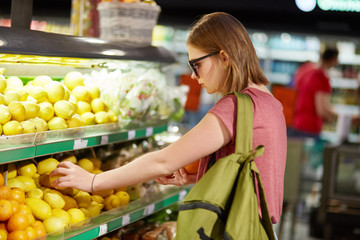 People, buying concept. Serious young cute female comes in food store for buying fruits, dressed in casual clothes, chooses lemons. Woman costumer makes purchase in supermarket. Healthy eating