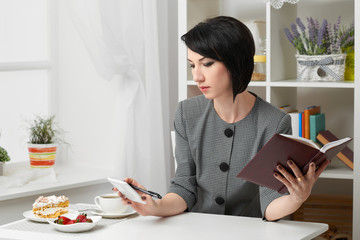 the business woman reading the diary, dressed in a gray suit poses in front of a white wall