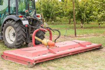 Sichelmäher an einem kleinen Traktor zur Bewirtschaftung einer Obstplantage