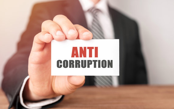 Businessman holding a card with text Anti Corruption