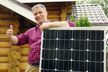 Solar panels in the hands of men . Energy production technologies. Wooden house background. The thumb of a person's hand upwards .