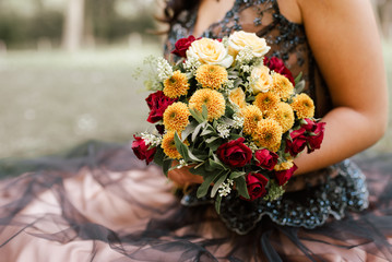 A bouquet of flowers in woman's hands. Vintage colors. Celebration/ special occasion concept.