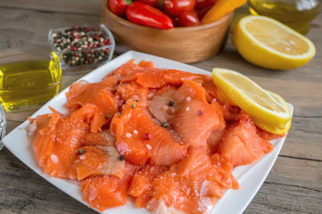 Raw pickled trout fillet and salmon pieces in a white plate. Wooden background.