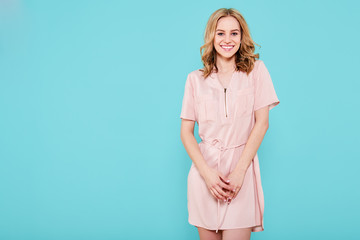 Beautiful smiling trendy teenage girl in pink summer dress looking at camera. Attractive young woman studio portrait isolated over pastel blue background. Confident woman.