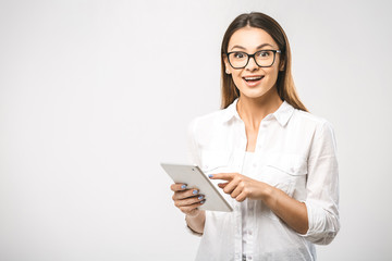 Portrait of a beautiful surprised woman using tablet computer isolated on a white background and looking at camera. Free space for text.