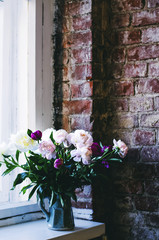 Bunch of colorful peony on window sill in loft interior