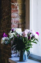 Bouquet of peonies in blue vase on windowsill, loft interior