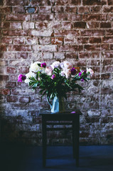 Peony flowers at vintage chair in loft interior, copy space on brick wall