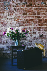 Loft interior with bunch of peony flowers, retro suitcase  and straw hat, copy space on brick wall