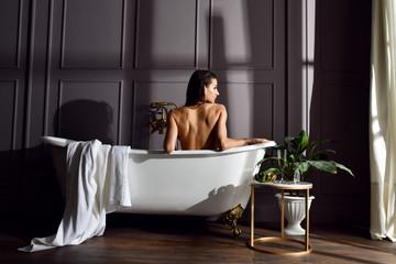 Young beautiful woman sitting in bathroom near expensive bathtub bath looking at the corner on dark