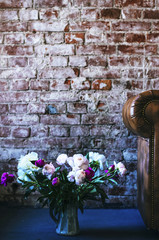 Loft lifestyle - leather sofa and bouquet of peonies on the floor