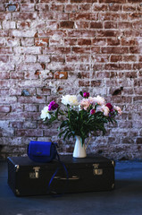 Loft style interior with bunch of flowers and retro suitcase decoration, copy space on brick wall