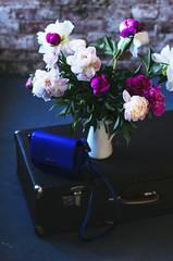 Bouquet of bright peonies in a vase in loft interior
