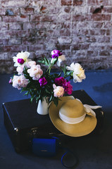Travel inspiration - bunch of peonies, vintage suitcase and straw hat in loft style interior