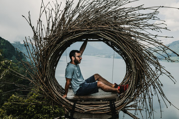 .Young tourist enjoying his tour of the island of Bali, Indonesia. Making a stop on a beautiful hill overlooking a large lake. Photographs in a straw nest, natural environment. Lifestyle