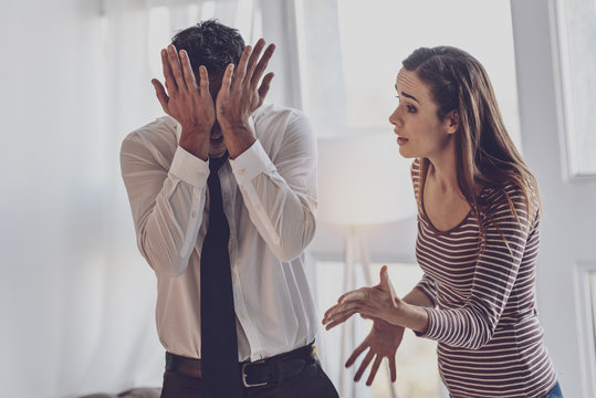 Family argument. Unhappy young woman shouting at her husband while having an argument with him