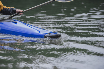 sport boat of a blue kayak in motion cuts the water surface with a bow.