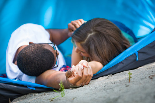 Intimate Multiethnic Young Adult Couple Camping and Holding Hands Laying In Tent