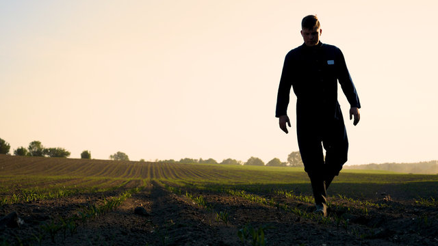 A young farmer in a blue robe walks the field looking at planted plants. Concept: clean air, bio, agriculture.