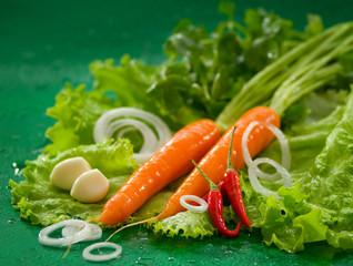 Мытая морковь на листьях зеленого салата, с чесноком и красным перцем чили на зеленом фоне Washed carrots on green lettuce leaves, with garlic and red chili on a green background