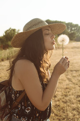 Young woman holding dandelion