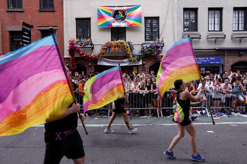 Participants walk past The Stonewall Inn during the 2018 New York City Pride Parade in Manhattan, New York