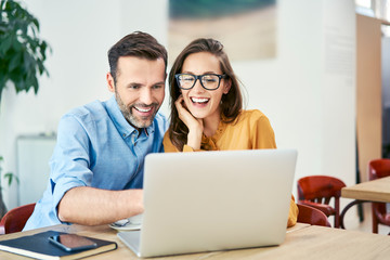 Portrait of cheerful couple using laptop together while sitting in cafe
